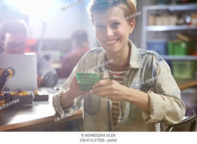 Portrait smiling female engineer assembling circuit board in workshop