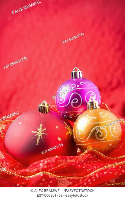 Baubles and red ribbon over a red background  Warm tones and a nice Christmas feeling