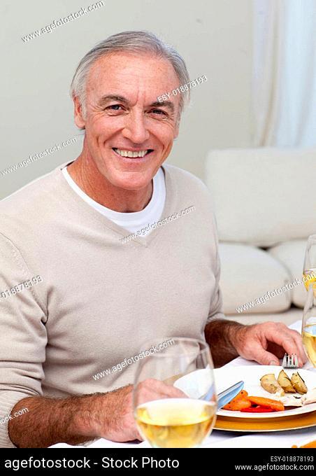 Senior man eating turkey in Christmas dinner