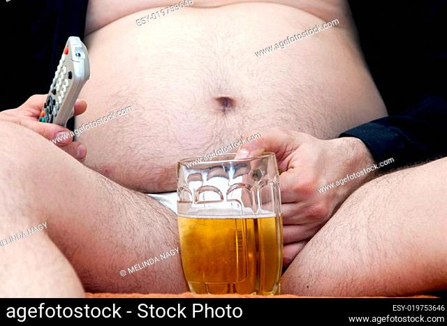 Overweight man sitting on the couch with a beer gl