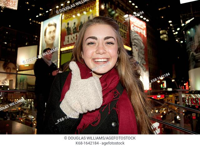 A girl smiles, and gives thumbs up, in Times Square, New York city, USA