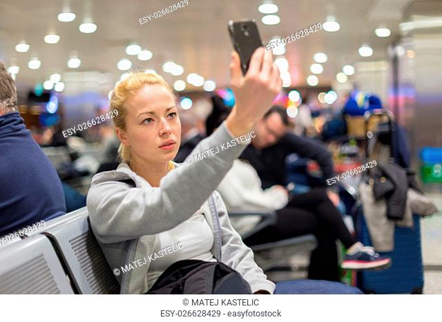 Casual blond young woman taking selfie photo using her cell phone while waiting to board a plane at the departure gates