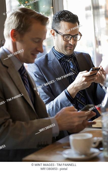 Business people in the city. Two men sitting at a cafe table checking their mobile phone messages and keeping in touch