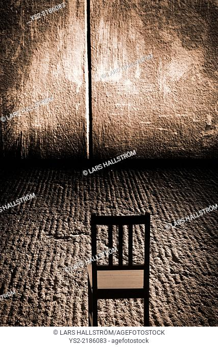 One empty chair in an abandoned room with concrete wall and rough grungy floor, possibly set up for interrogation. Conceptual image of loneliness