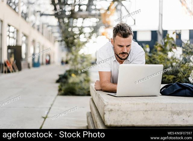 Young man with laptop and looking sideways, lying on a bench in the city