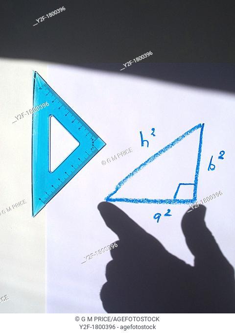 shadow hand measuring Pythagorean triangle drawn in blue crayon