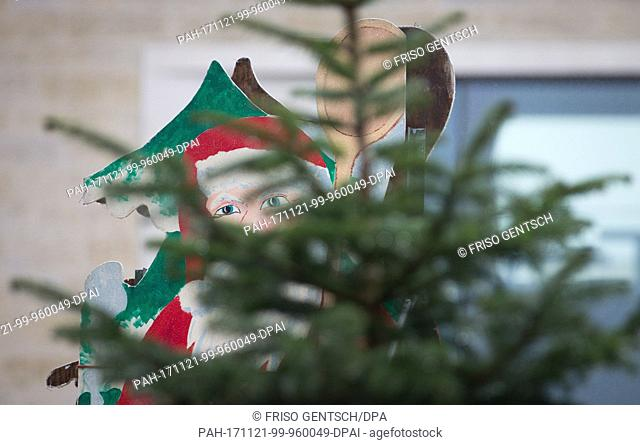 A wooden Santa Clause with cooking spoons peeks through a christmas tree in Muenster, Germany, 21 November 2017. In many cities the Christmas market set up...