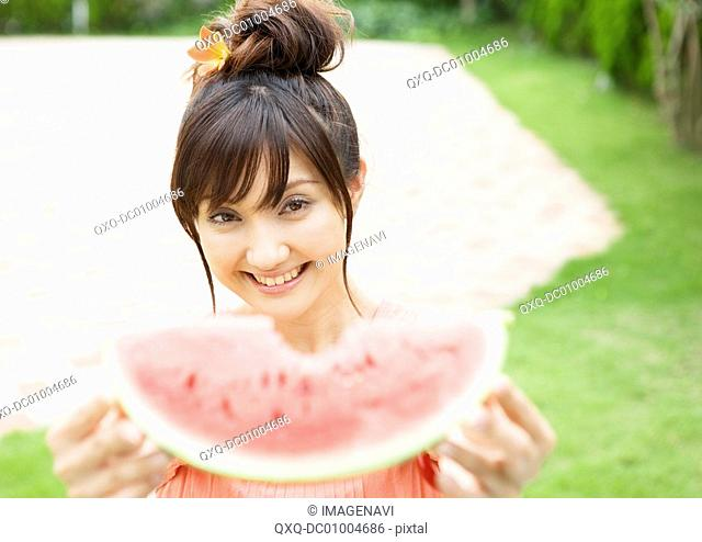 A woman eating watermelon