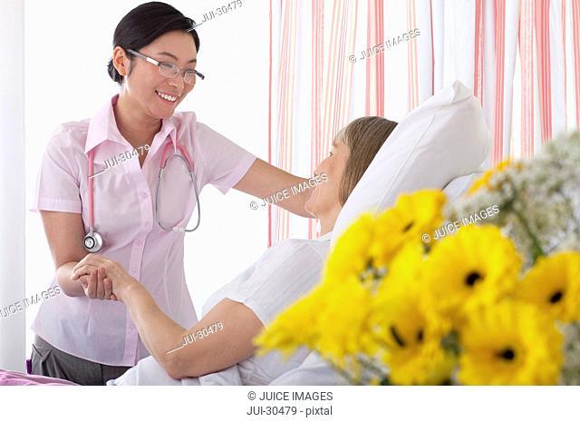 Nurse comforting patient in hospital room
