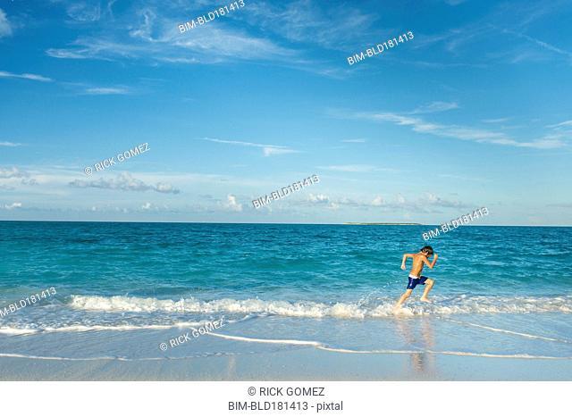 Hispanic boy running on beach