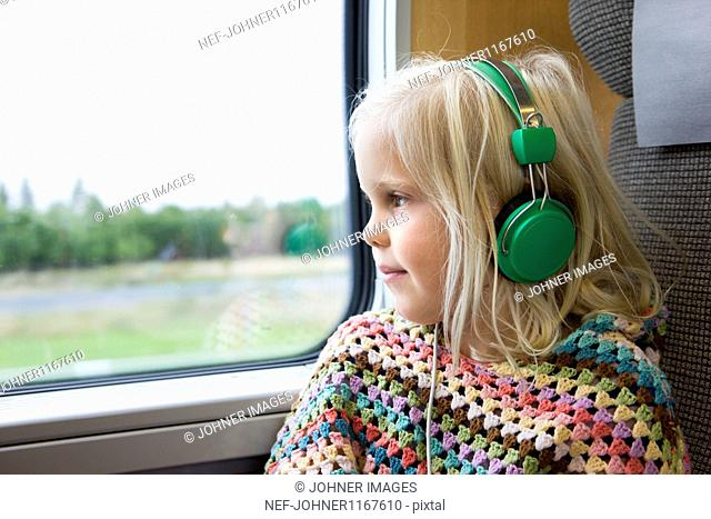 Girl listening to music while traveling on high speed train