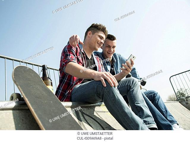 Young men in skatepark, using smartphone, drinking bottle of beer