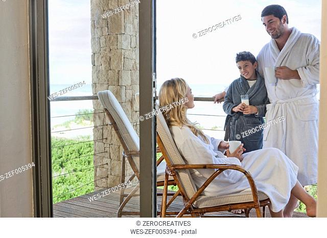 Family wearing bathrobes on patio of beach house