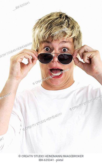 Young man looking over his sunglasses, astonished