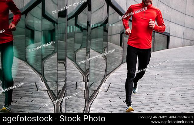 Unrecognizable male athlete running near glass wall
