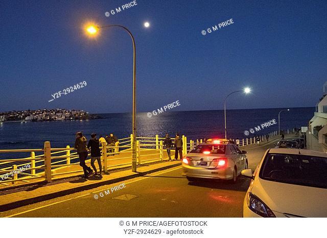 people look over Bondi Beach on moonlit evening, Sydney