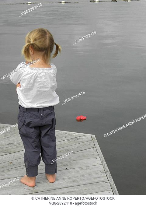 Fed up little girl with bunchies who's shoe has fallen in the water, coastal village near Gothenburg, Sweden