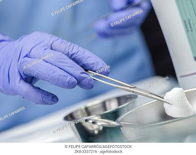 Surgeon working in operating room, hands with gloves holding scissors with torunda, conceptual image, horizontal composition