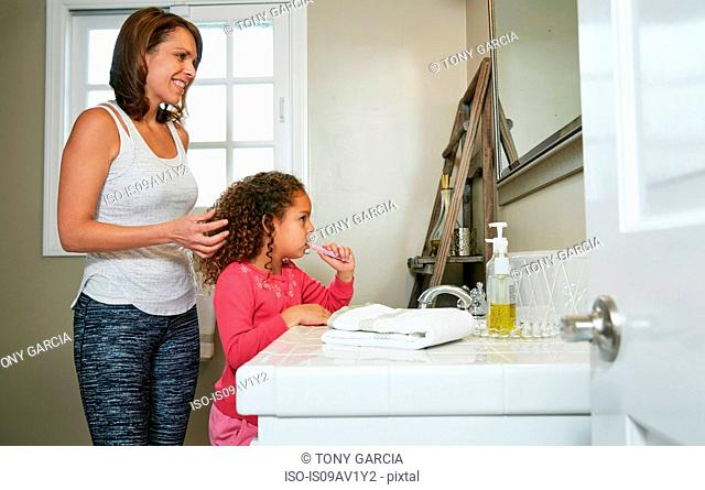 Mother and daughter in bathroom at sink brushing teeth