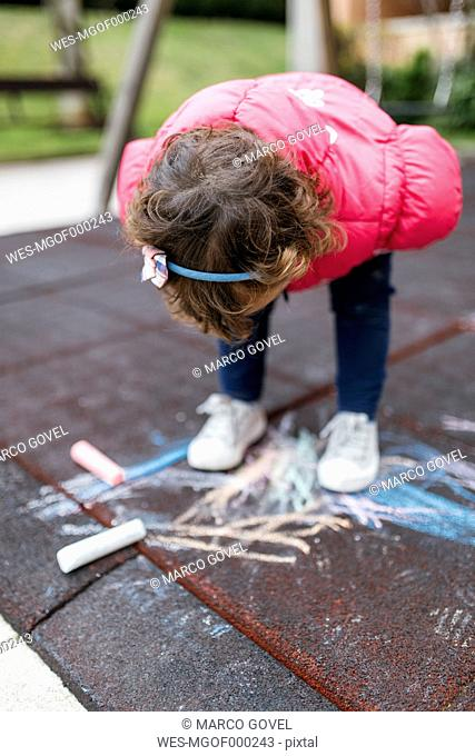 Spain, Little girl drawing with chalk on the ground