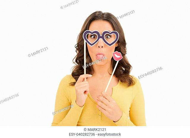 Party image. Playful young women holding a party glasses and fake lips in front of her face while isolated on white