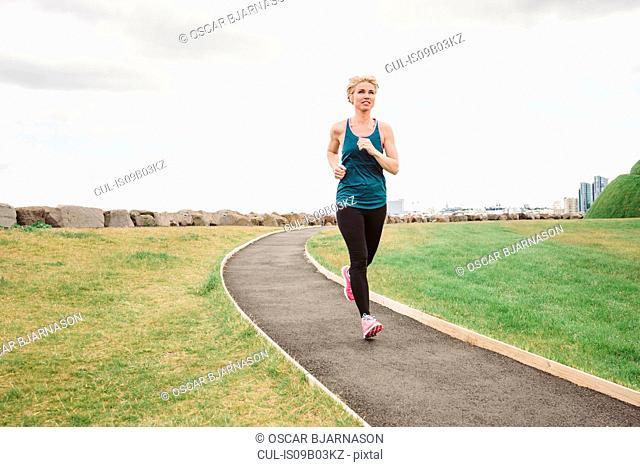 Female runner running on coast path, Reykjavik, Iceland