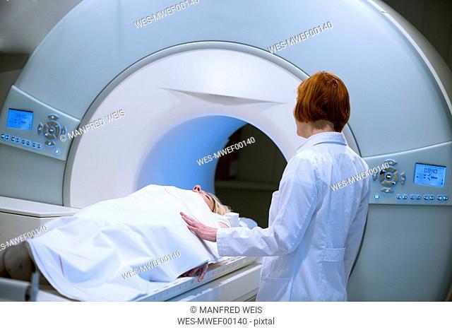 Female doctor preparing patient for magnetic resonance imaging
