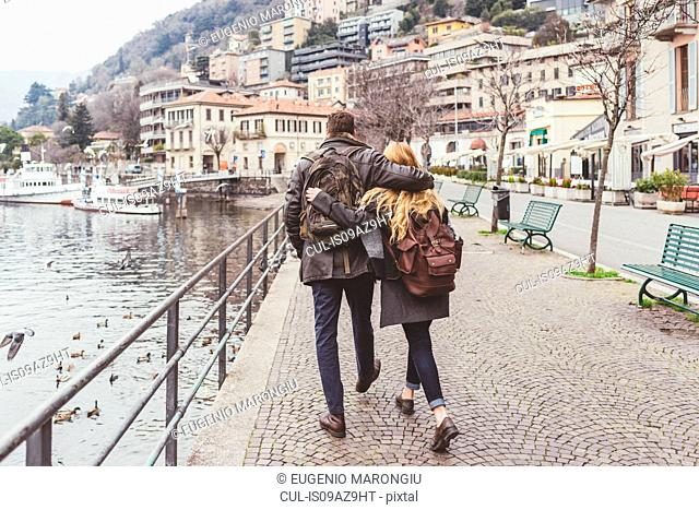 Rear view of young couple strolling along lakeside, Lake Como, Italy