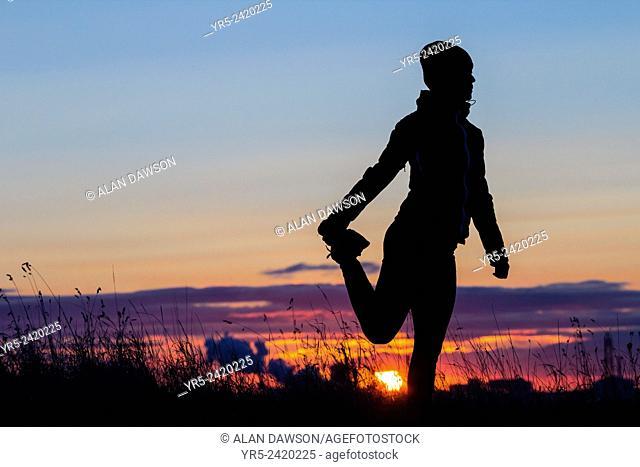 Female jogger stretching at sunrise. Cowpen Woodland Park, Billingham, England, United Kingdom