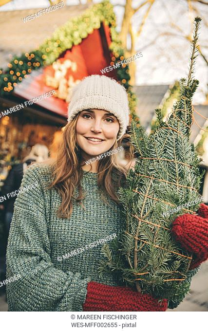 Smiling woman with a wrapped-up tree standing on the Christmas Market