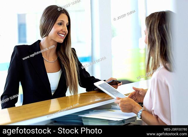 Smiling businesswomen talking to woman at reception desk