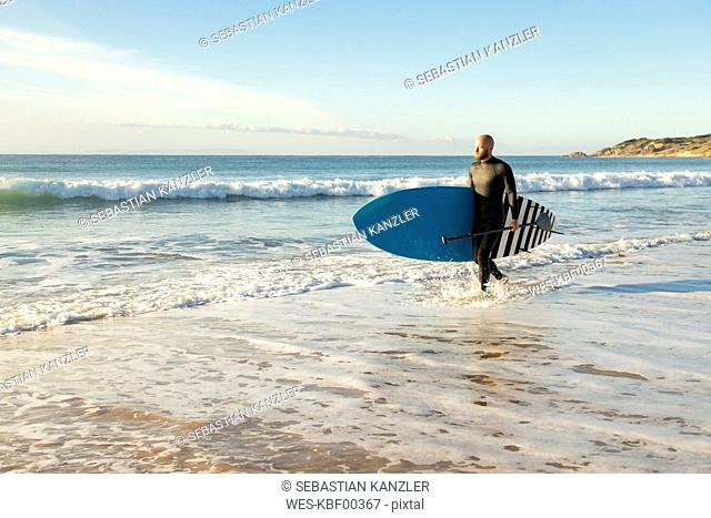 Spain, Andalusia, Tarifa, man walking with stand up paddle board at the sea