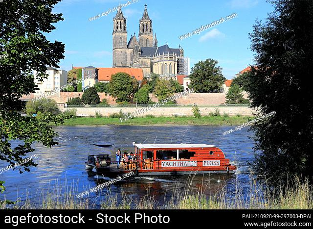 28 September 2021, Saxony-Anhalt, Magdeburg: A party raft sails upstream across the Elbe past Magdeburg's cathedral of St. Maurice and St. Catherine