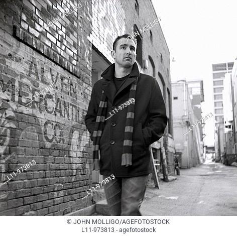 Man in peacoat, walking through alley