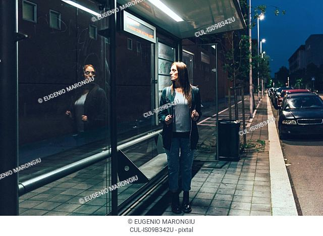 Young woman looking at reflection whilst waiting at bus stop at night