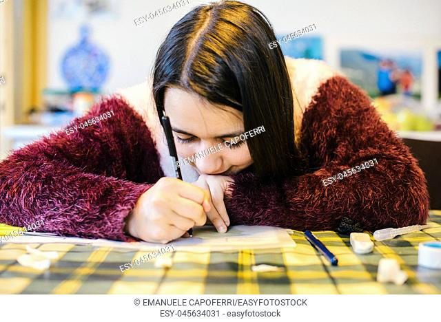 teen ager girl carries out school homework-little girl is studying at home-portrait of little girl writing