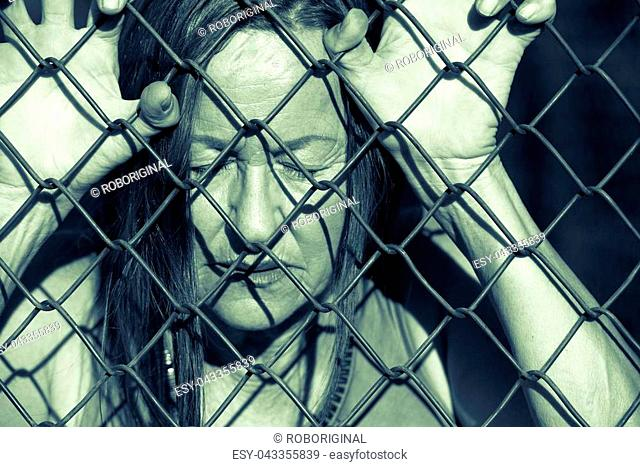 Filtered image Portrait of devastated, stressed mature woman with closed eyes and hands gripped on behind mesh wire fence