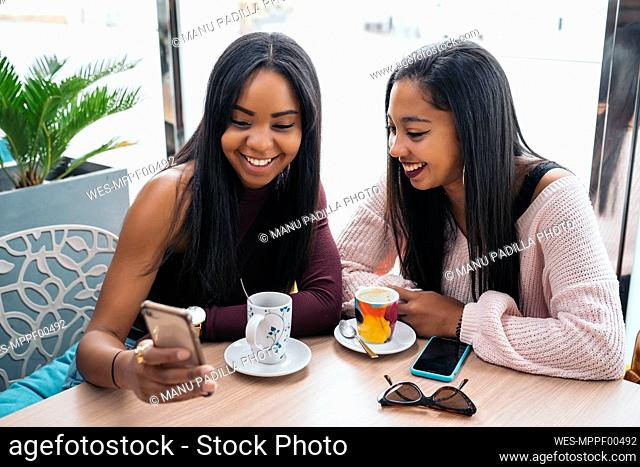 Two happy young women sharing cell phone in a cafe