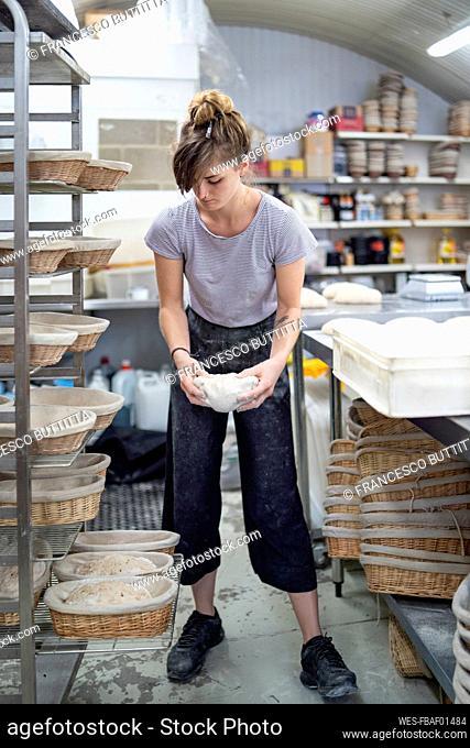 Woman preparing bread in bakery