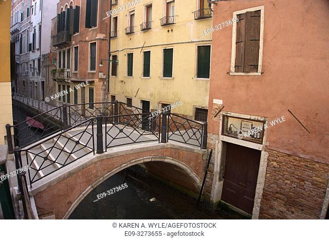short bridge over narrow canal, yellow and rust-red buildings, muted colors, Venice, Italy