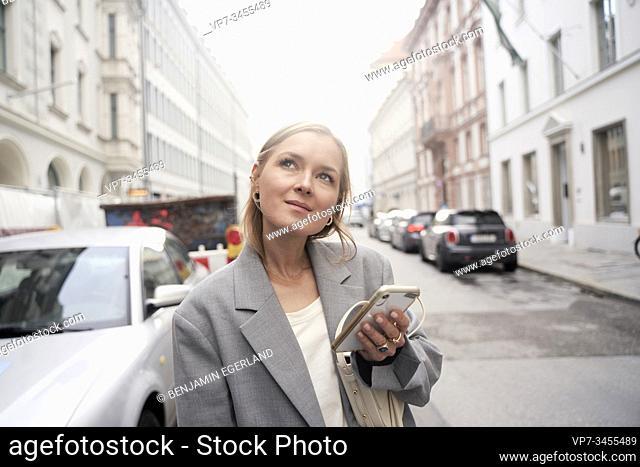 Stylish woman using smartphone in city. Munich, Germany
