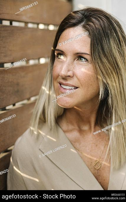 Close-up of smiling thoughtful woman looking away