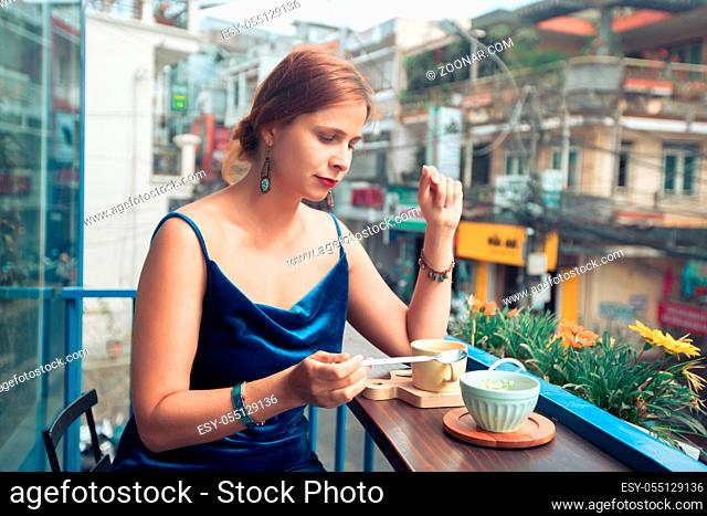 Beautiful woman enjoying tea and dessert on cafe terrace in Dalat, Vietnam