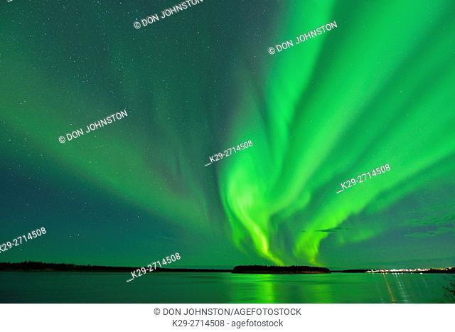 Aurora borealis (northern lights) in the night sky over the MacKenzie River with the town lights of Fort Providence, Fort Providence, Northwest Territories