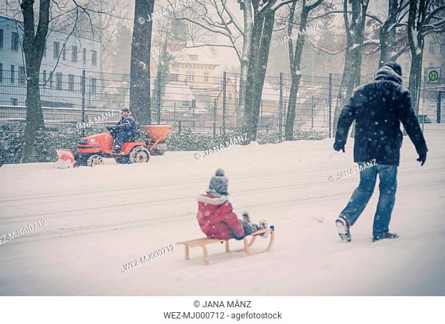 Father pulling sledge with son in snow