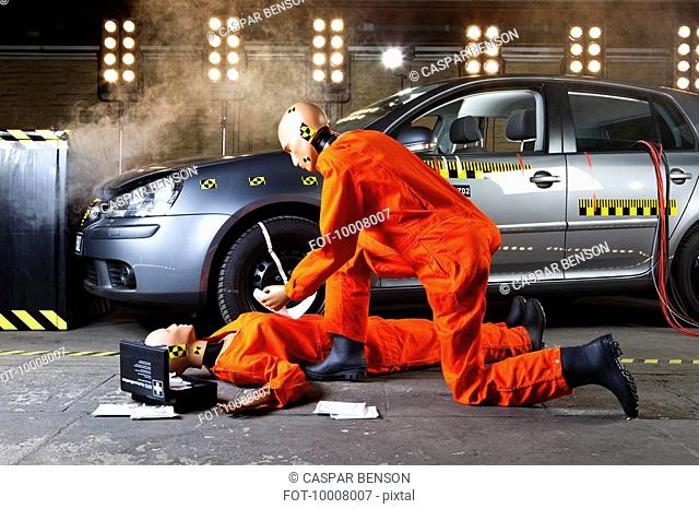A crash test dummy administering first aid on another