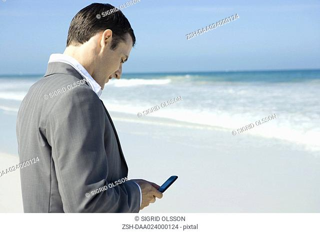 Businessman on beach, using cell phone