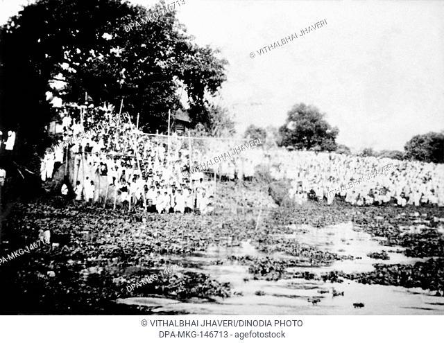 Crowds standing next to a river where Mahatma Gandhis ashes dissolve ; Dhaka ; February 1948 NO MR