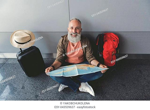 Cheerful bearded tourist is sitting in waiting hall. He choosing future route for trip and looking at camera with smile. Waist up portrait. Top view
