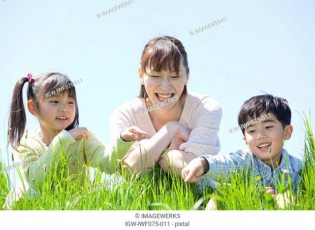 Japan, Tokyo Prefecture, Mother and children in meadow looking at grass, smiling
